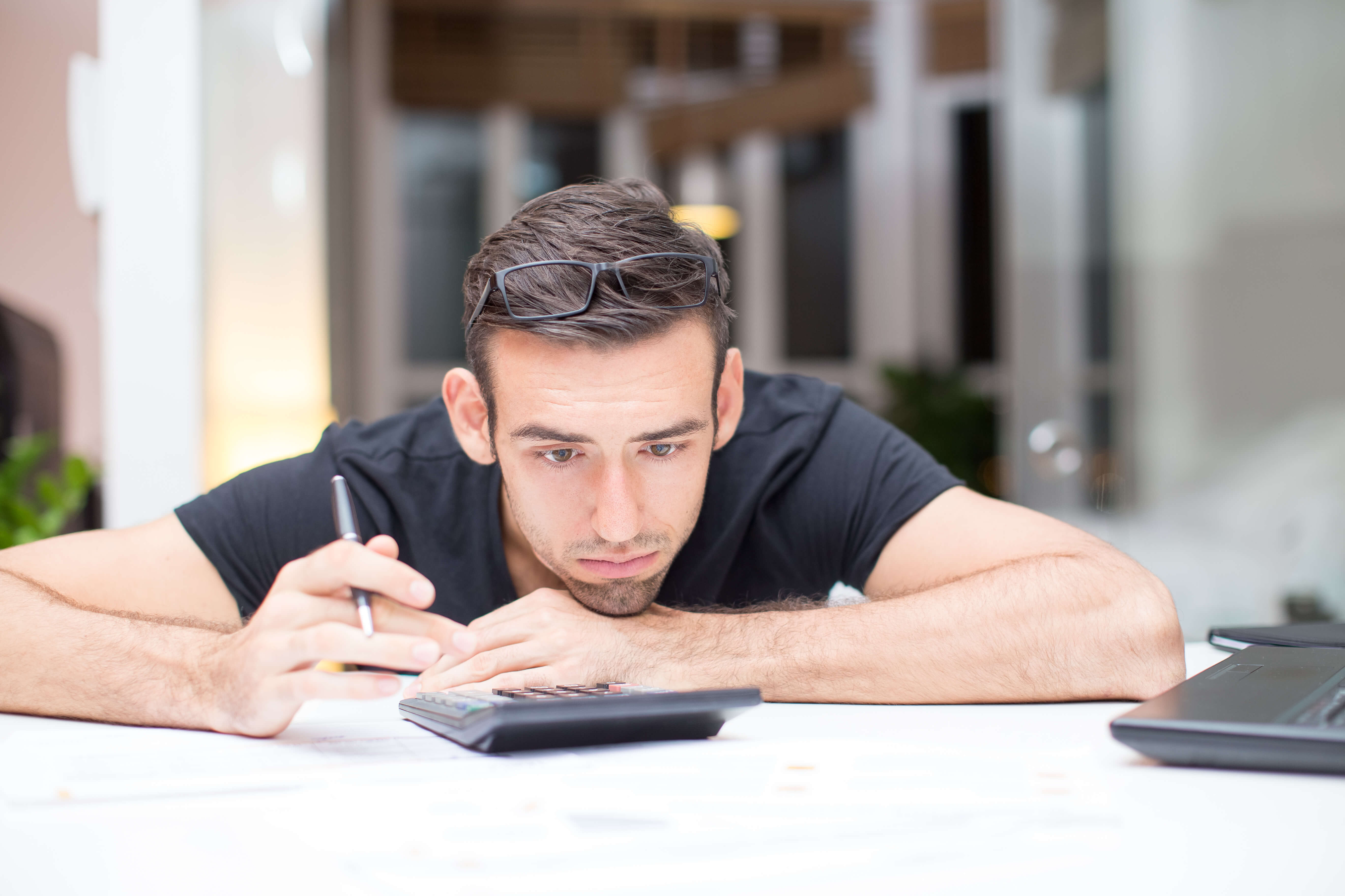 Closeup portrait of tired young handsome man lying on table with calculator in office