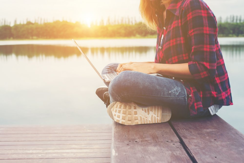 Young happy hipster woman working with her laptop sitting on pier,relaxing enjoy with nature.