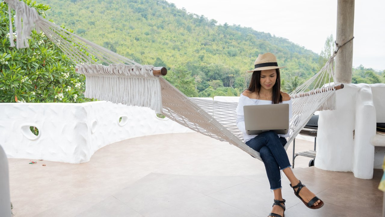 Young woman enjoys a laptop in a hammock on the beach