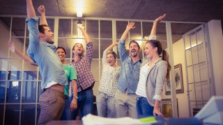 Creative business team waving their hands together at the office